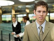 Young businessman, portrait, women in background