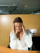 Young woman sitting at desk having head ache