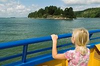 Girl watching the islands from a small car ferry. Sweden