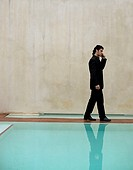 Businessman talking on his cell phone by swimming pool