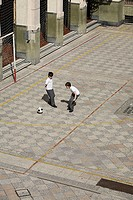Young students playing soccer in courtyard