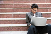Businessman using laptop on staircase
