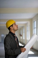 Businessman in hardhat reading blueprints