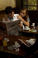 Couple reading a newspaper in cafe