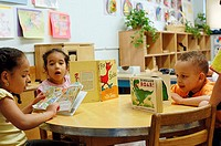 Children reading or selecting books to read during library time at Marble Hill Nursery School, Bronx, NY