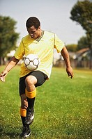Soccer player bouncing soccer ball on knee