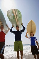 Three generations carrying surfboards