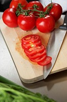 Tomatoes on a carving board next to a kitchen knife, high angle view