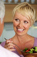 Blond woman with a salad smiling at a man, selective focus, close-up