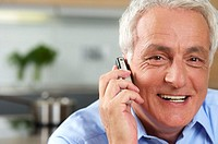 Grey-haired man is using his mobile phone, smiling