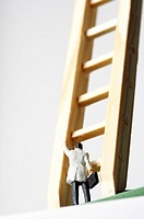 Businessman figurine in front of a ladder