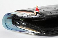 Businesswoman figurine sitting on a wallet with banknotes