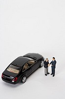 Two businessmen figurines shaking hands in front of a car