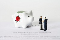 Businessmen figurines and piggy bank on an agreement