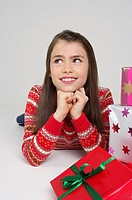 Smiling girl lying on front next to Christmas presents