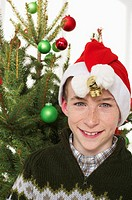 Boy wearing Santa hat in front of a Christmas tree