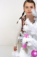 Girl next to a white Christmas tree