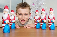 Boy smiling at camera, Santa Claus chocolates on a table
