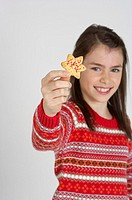 Girl holding a Christmas cookie at camera