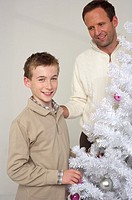 Father and son next to a white Christmas tree