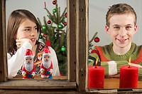 Girl and boy looking out of a window with candles and Santa Claus chocolates
