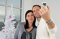 Couple photographing themselves with a mobile phone in front of a white Christmas tree