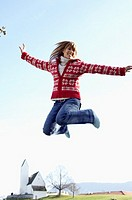Young woman jumping into the air in front of a small town