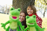 Two young women with frog hand puppets, selective focus