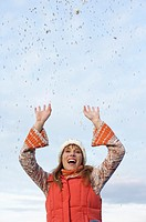 Young woman with scarf and cardigan under the sky while playing with confetti, close-up