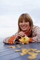 Young woman sitting at a table with golden chocolate coins, selective focus