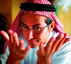 Arab man gesturing and looking over his glasses