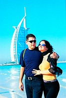 Western tourist couple on the beach near Burj Al Arab hotel in Dubai, UAE