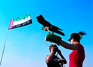 Western tourists holding a falcon on gloved arm, United Arab Emirates