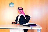 Saudi Arabian businessman checking time on wall clock (thumbnail)