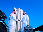 Saudi businessmen shaking hands in front of NCB building, Jeddah, Saudi Arabia