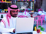 Saudi man working on laptop and smoking shisha in Old Town of Jeddah, Saudi Arabia