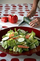 Close-up of a salad on a plate with a person cutting slices of cucumber in the background