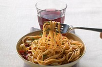 Spaghetti with dried peppers, glass of red wine