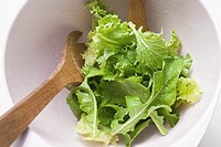 Mixed salad leaves in bowl with salad servers