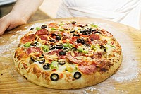 Hands holding pepperoni pizza with peppers and olives (thumbnail)