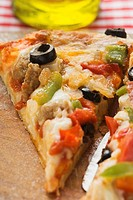 Piece of pepperoni pizza with peppers and olives