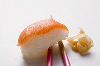 Nigiri sushi with salmon on chopsticks and preserved ginger
