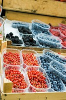 Various types of berries in plastic punnets at a market (thumbnail)