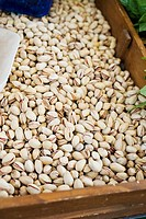 Pistachios in a wooden box at a market (thumbnail)