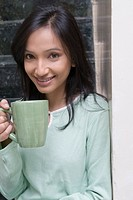 Portrait of a young woman holding a cup of coffee and smiling