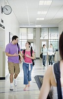 Male and female students talking in hallway