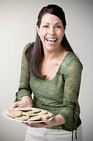 Hispanic woman holding plate of cookies