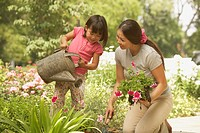 Asian mother and young daughter gardening