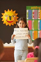 Young Hispanic girl holding up paper in class