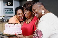 Three middle-aged African women holding cake